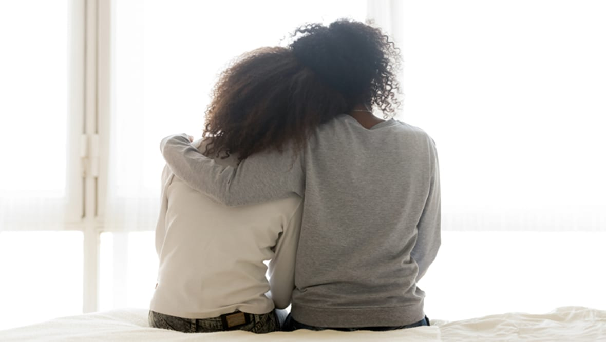 Woman with her arm around another woman